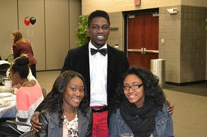 Three student smile for the camera at the Black Heritage Dinner.