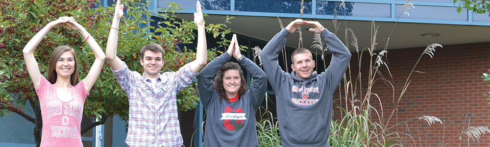 Four students pose the O-H-I-O